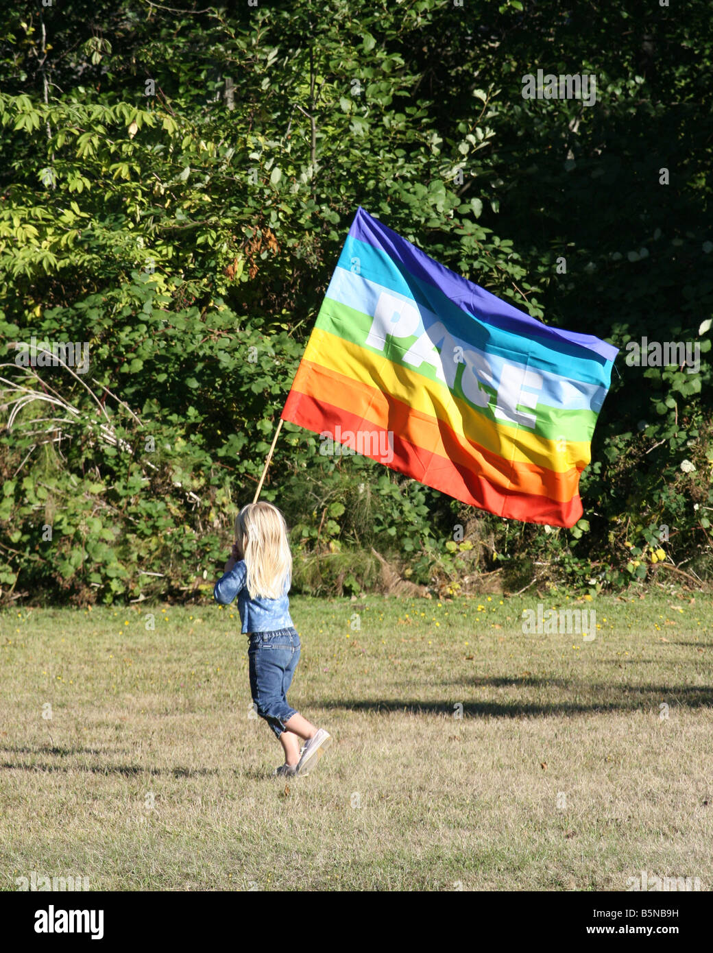 Peace march with young girl walks alone with a peace flag in the bright sun. - Stock Image