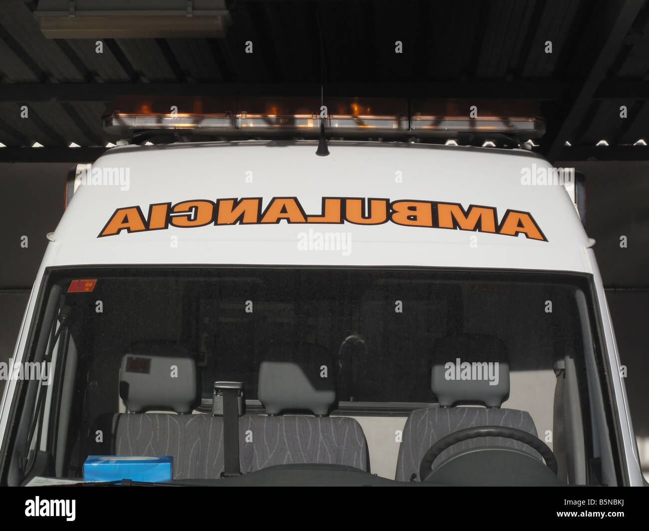Spanish word for ambulance written backwards on vehicle so that drivers ahead can recognize word in their rear vision - Stock Image