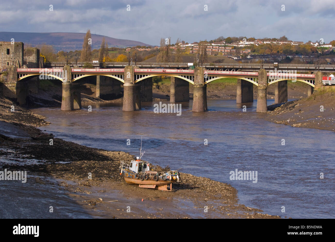 Small boat aground used for removing rubbish from the mud of the tidal River Usk in Newport city centre South Wales - Stock Image