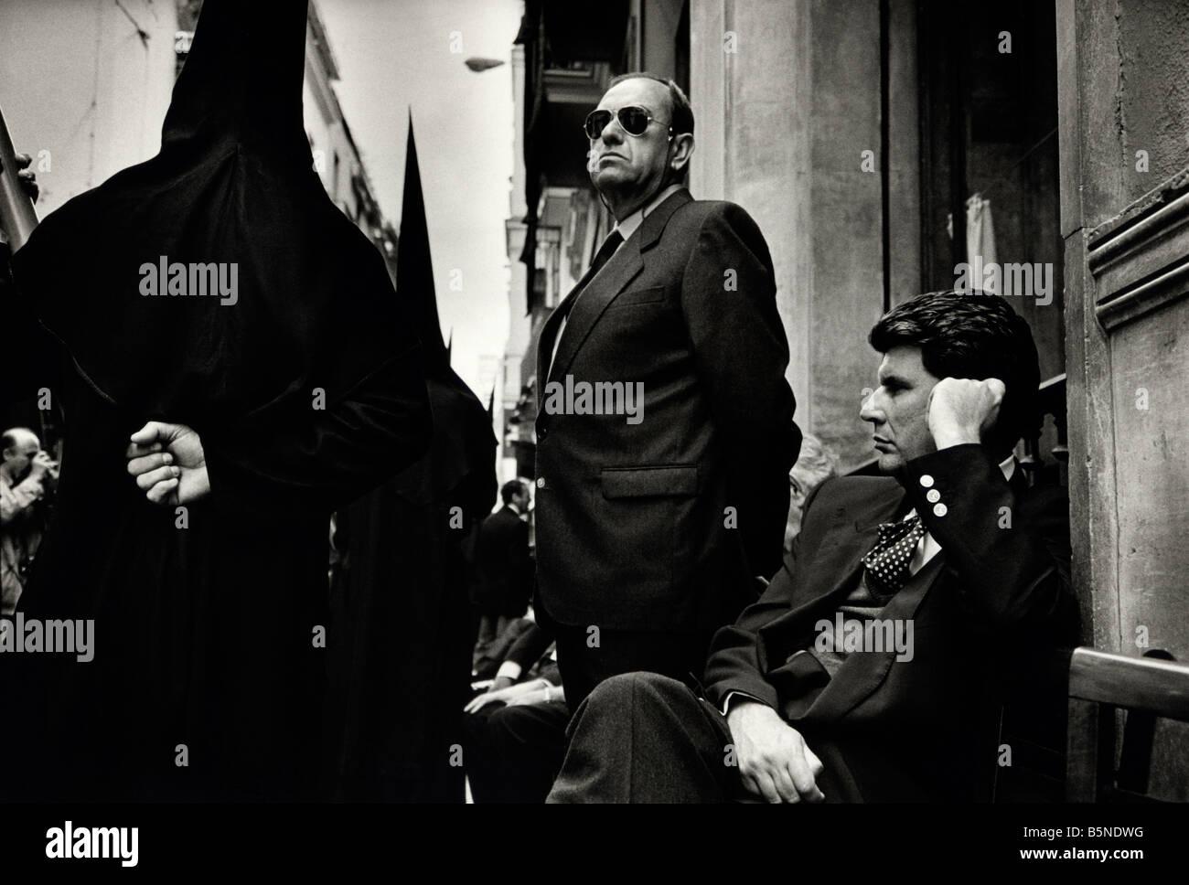 Members of the Brotherhood pass men on street during Semana Santa processions. Seville, Spain. - Stock Image
