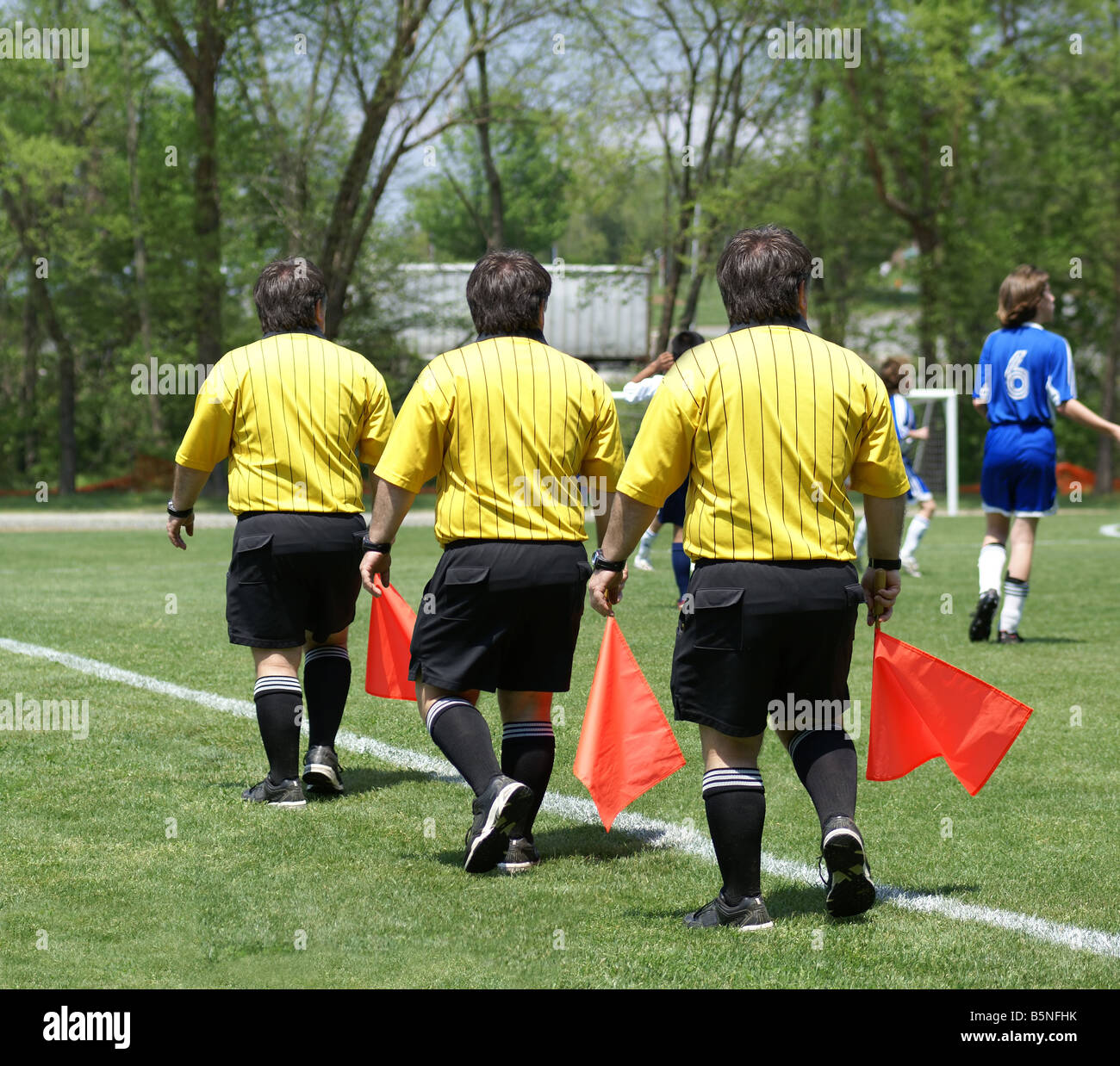 Triplet soccer side referee with red flag. Composition with three positions of the side ref, perfectly blended into - Stock Image
