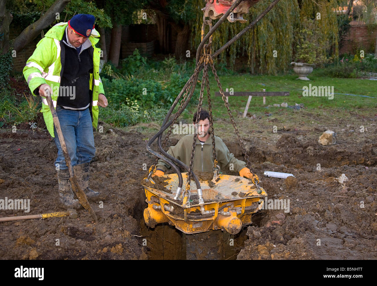 Workmen fitting a pile crusher over a pile, - Stock Image