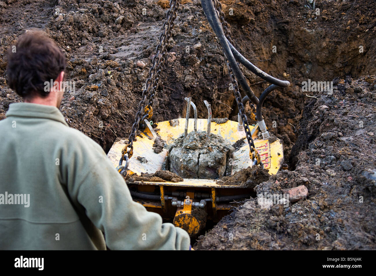 A pile crusher in place, slowly crushing the concrete before it can be removed. - Stock Image