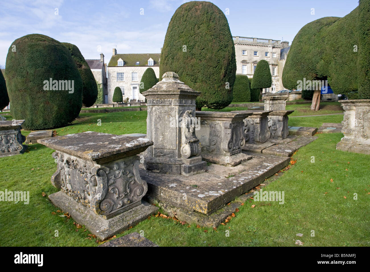 Pedestal and table tombs amongst yew trees St Marys Church Painswick Cotswolds UK - Stock Image