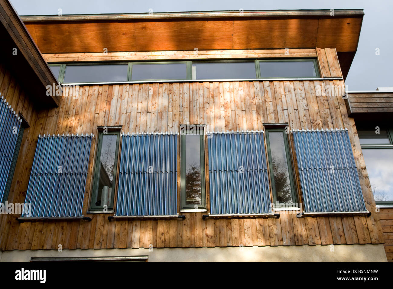 Vertically wall mounted solar thermal evacuated tubes The Green Shop Bisley Stroud UK - Stock Image