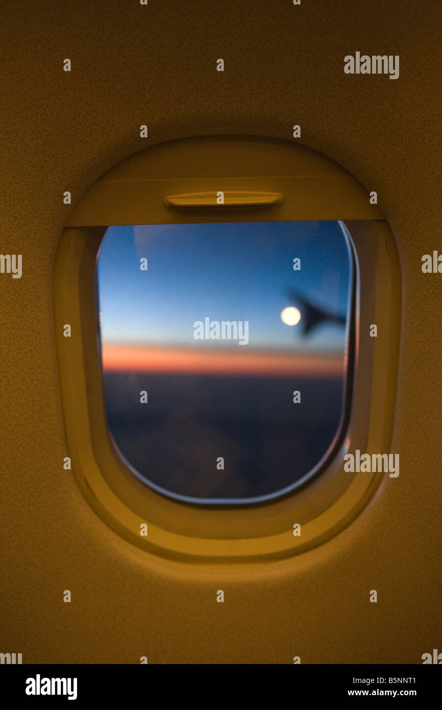 TWILIGHT VIEW THROUGH COMMERCIAL AIRLINER PASSENGER CABIN WINDOW FRAME - Stock Image