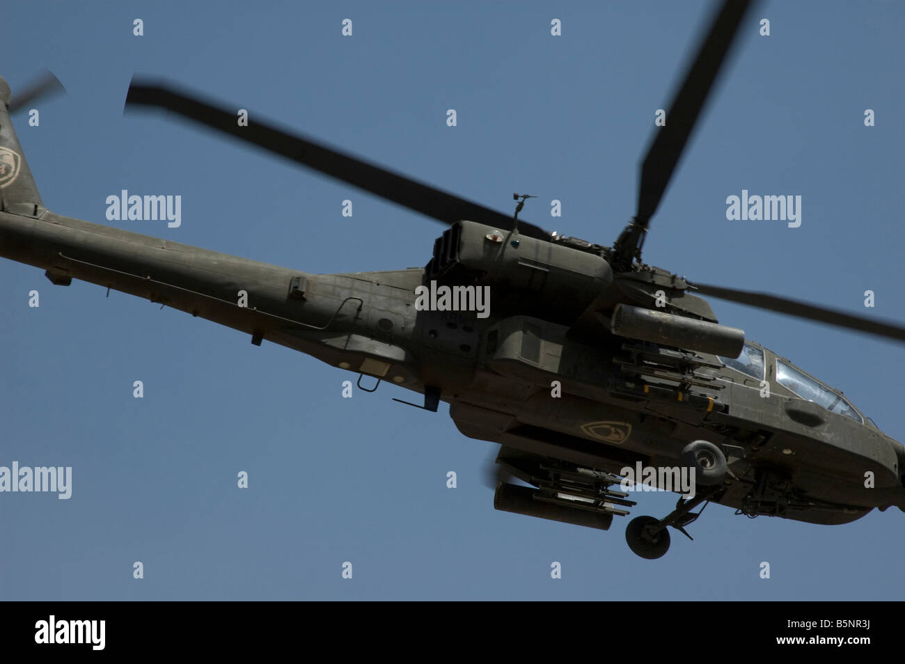 AH 64 Apache Helicopter overflying the green zone in baghdad against a blue sky - Stock Image