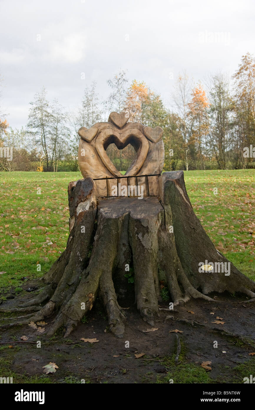 A 'Love Seat' carved into a tree stump with a heart shaped hole, in Edenvilla Park, Portadown, scupltured - Stock Image