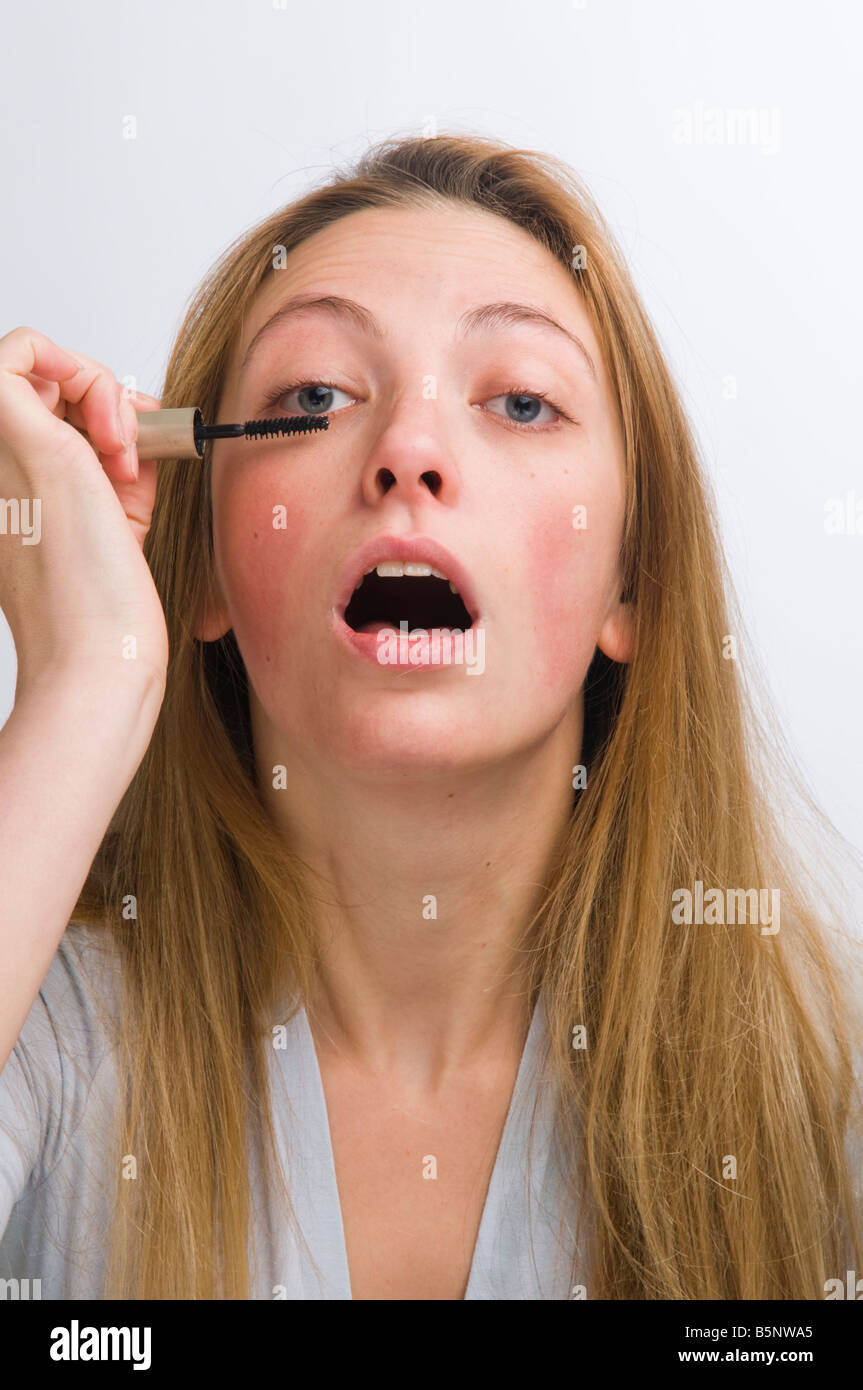 young blonde haired woman applying mascara to her eyelashes; putting on make-up - Stock Image
