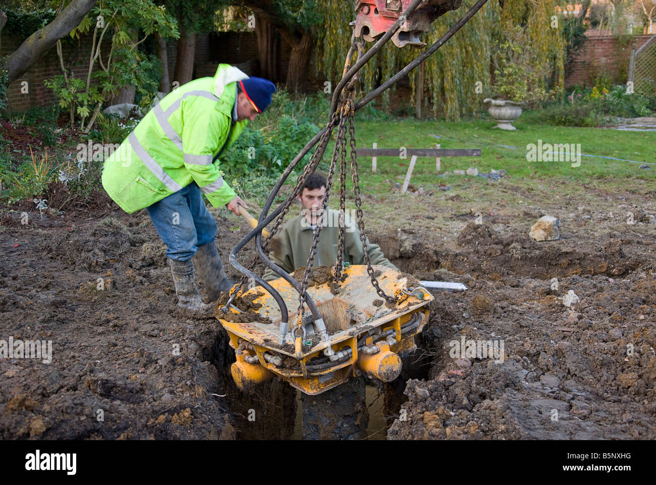 Workmen manoeuvrering a pile crusher into position - Stock Image