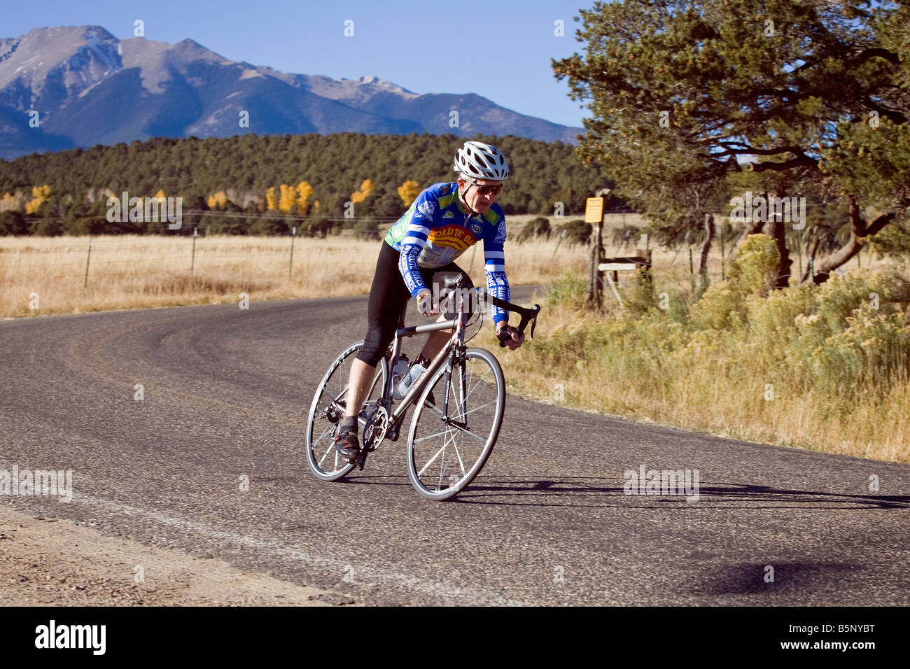 Male bicyclist riding down a rural gravel road near Salida, Colorado, USA - Stock Image