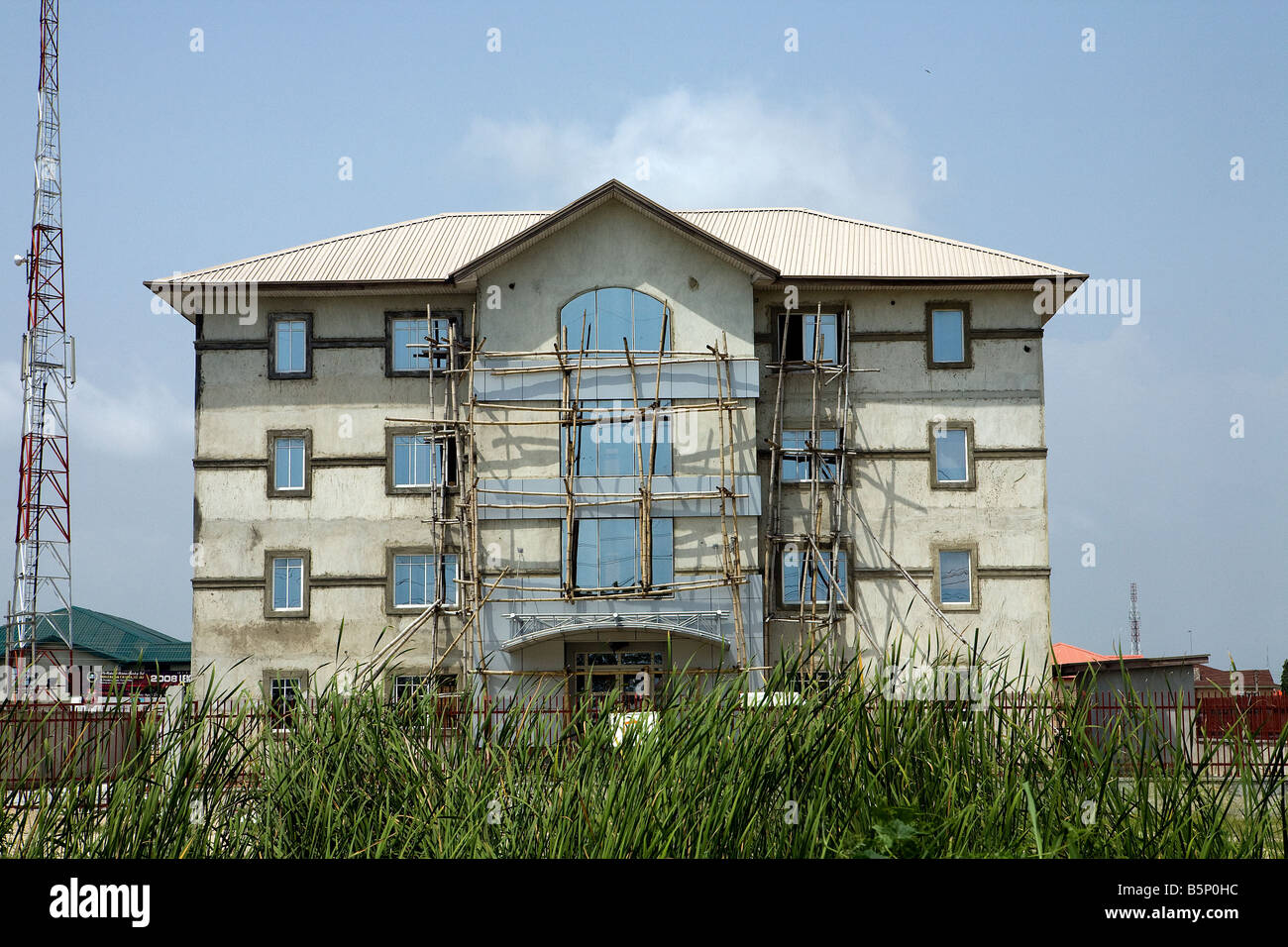 A new four-floor building is nearly completed and still has some of the bamboo scaffolding erected - Stock Image