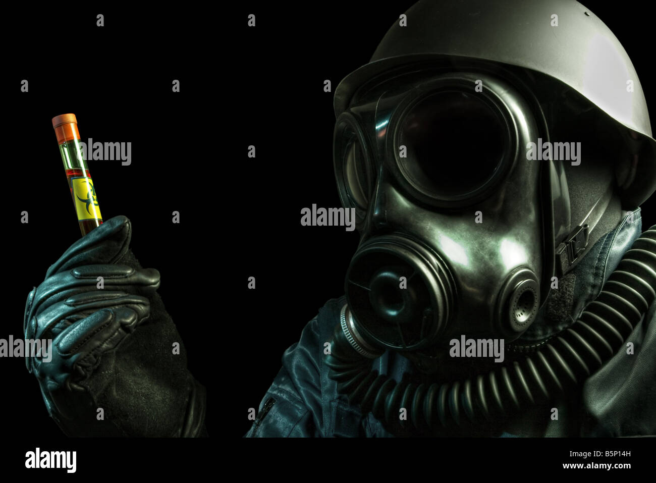 Gas masked man holding a test tube with biohazard symbol - Stock Image