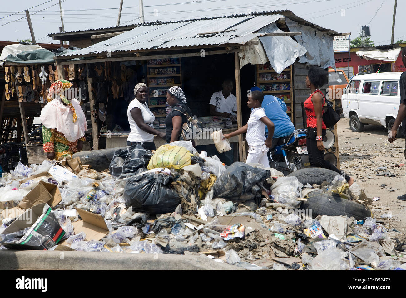 A crowd of people walk past a Nigerian market stall which has a rubbish tip in front - Stock Image
