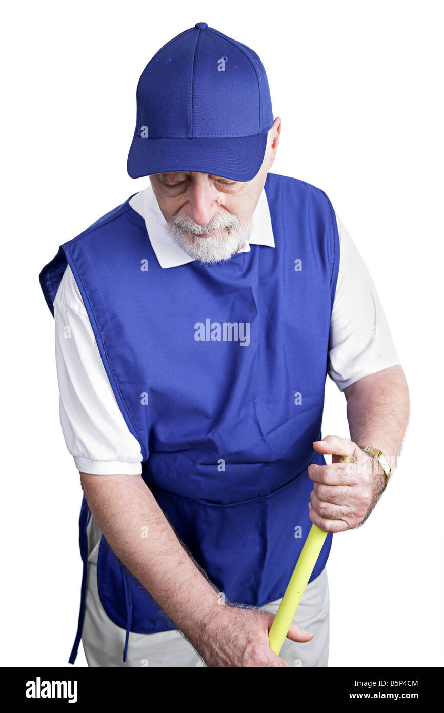 A senior man sweeps up on his menial service job Isolated on white - Stock Image