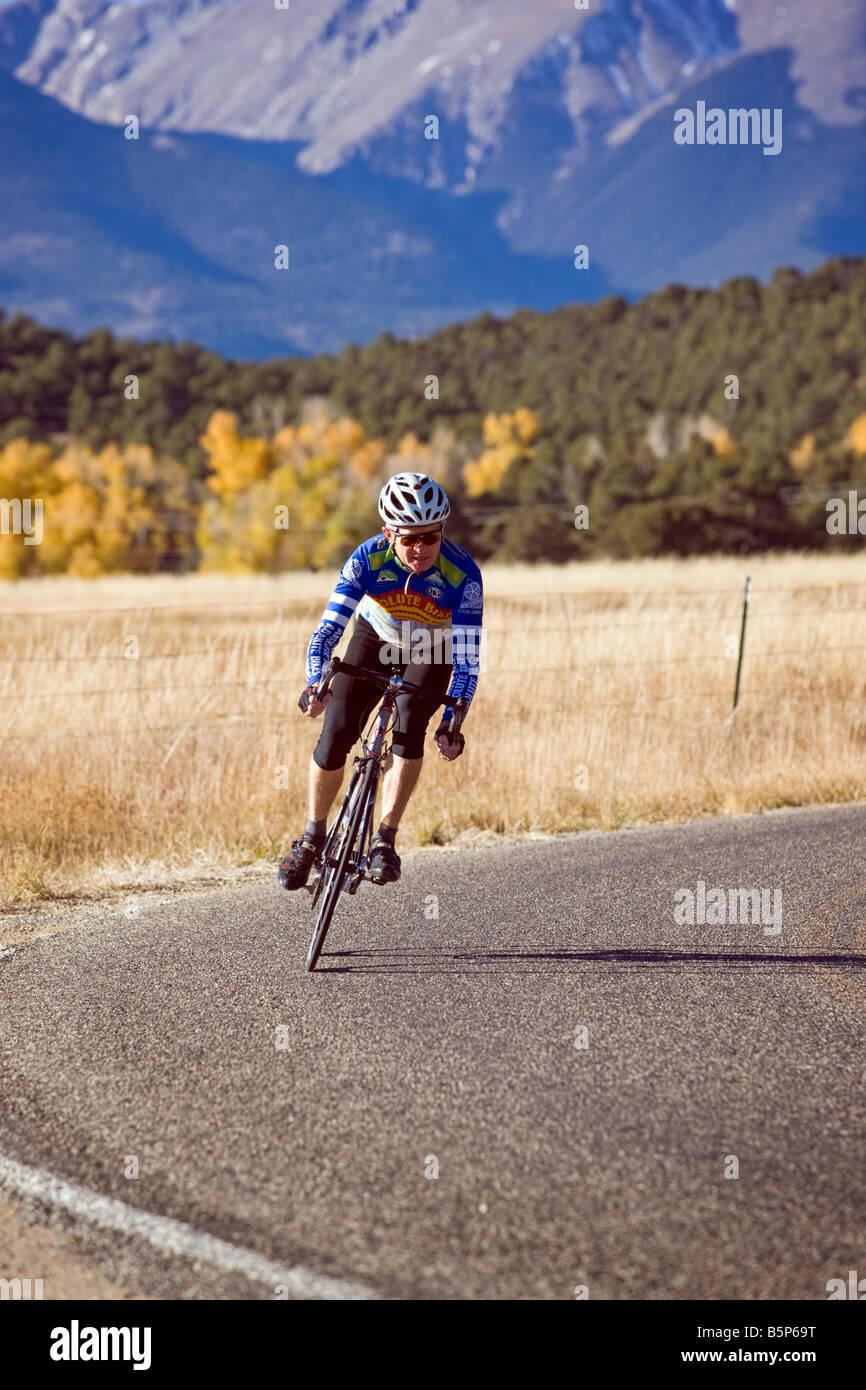 Male bicyclist riding down a rural gravel road near Salida, Colorado, USA - Stock Image