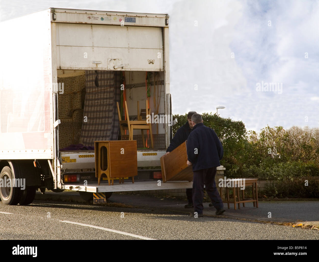 North Wales UK  Two men loading unwanted furniture into a van for re-using reduces landfill local recycling - Stock Image