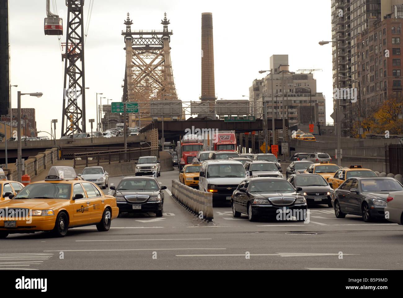Traffic exits the Queensborough Bridge into New York - Stock Image