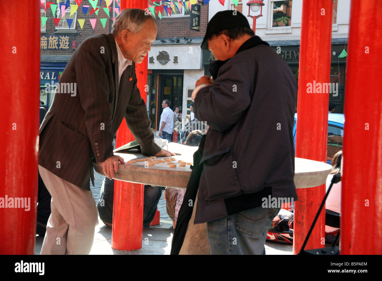 Chinese men play game of draughts in London's Chinatown - Stock Image