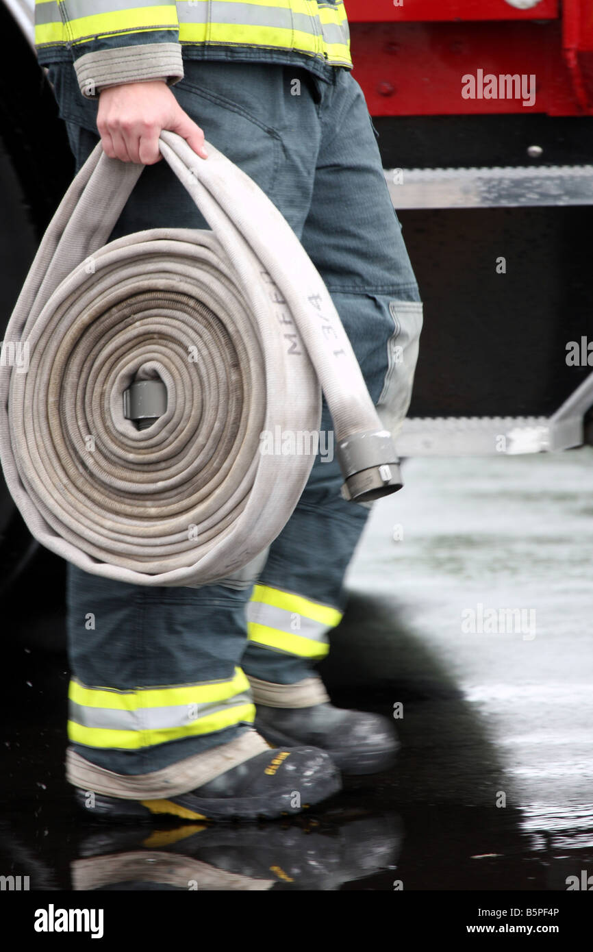 A firefighter carrying the hose of a fireline at a scene after it has rained Feet are blurred with speed - Stock Image