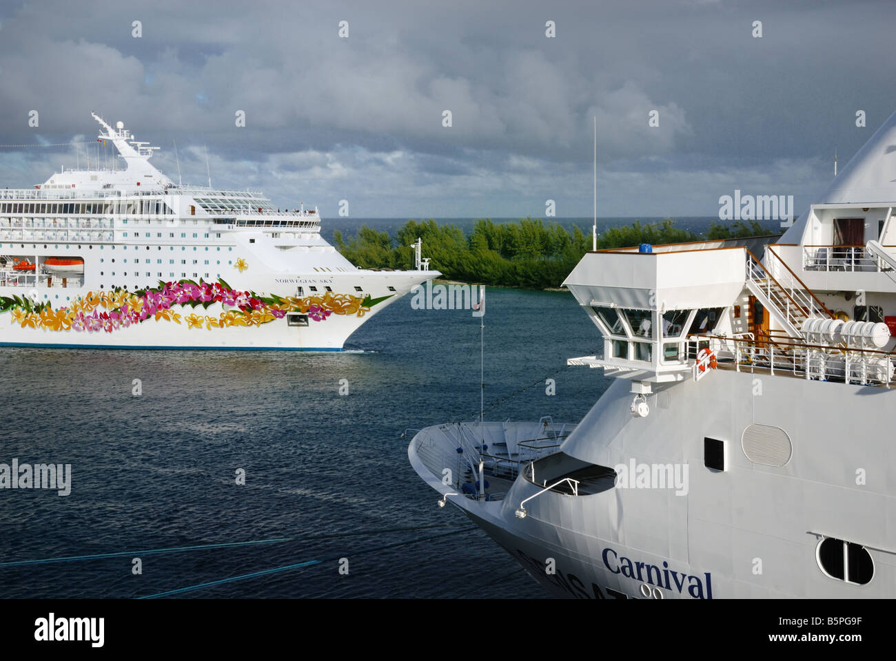 The Norwegian Sky cruise ship passes by a docked Carnival cruise ship in Nassau, Bahamas. - Stock Image