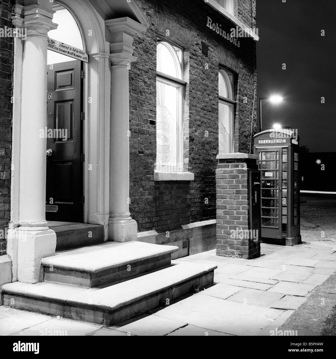 UK Cheshire Stockport Hillgate K6 phone box outside Star and Garter pub at night black and white - Stock Image