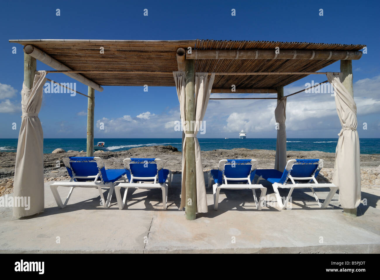 Four lounge chairs under a beach hut at Little Stirrup Cay.  Cruise ship Majesty of the Seas can be seen in the - Stock Image