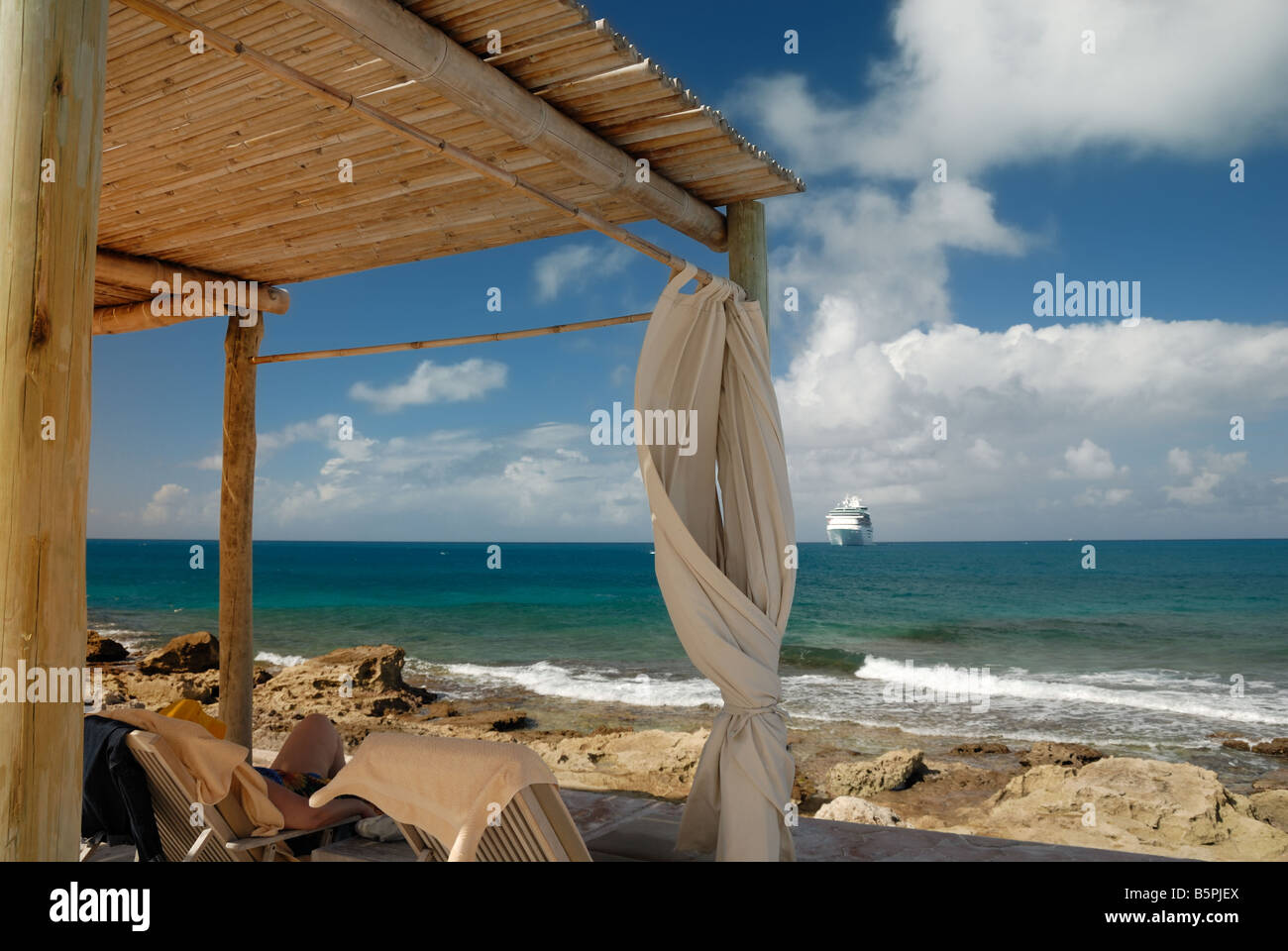 A traveler lounges in a hut on the beach at Little Stirrup Cay.  Cruise ship Majesty of the Seas can be seen in - Stock Image