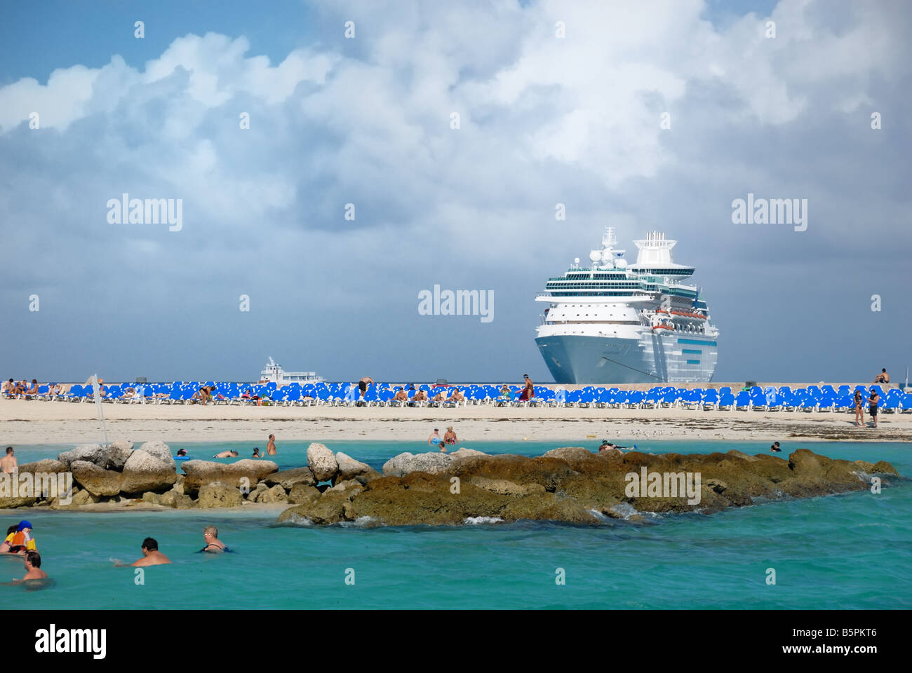 The Royal Caribbean cruise ship Majesty of the Seas can be seen in the distance from the beach at Little Stirrip - Stock Image