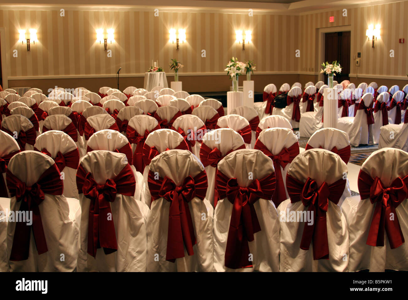 The chairs with red bows set up for a wedding ceremony - Stock Image