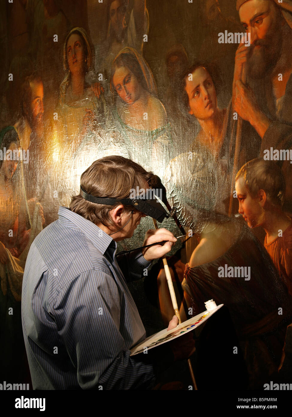 Restorer retouching a large painting by Dutch master Petrus van Schendel Breda the netherlands - Stock Image