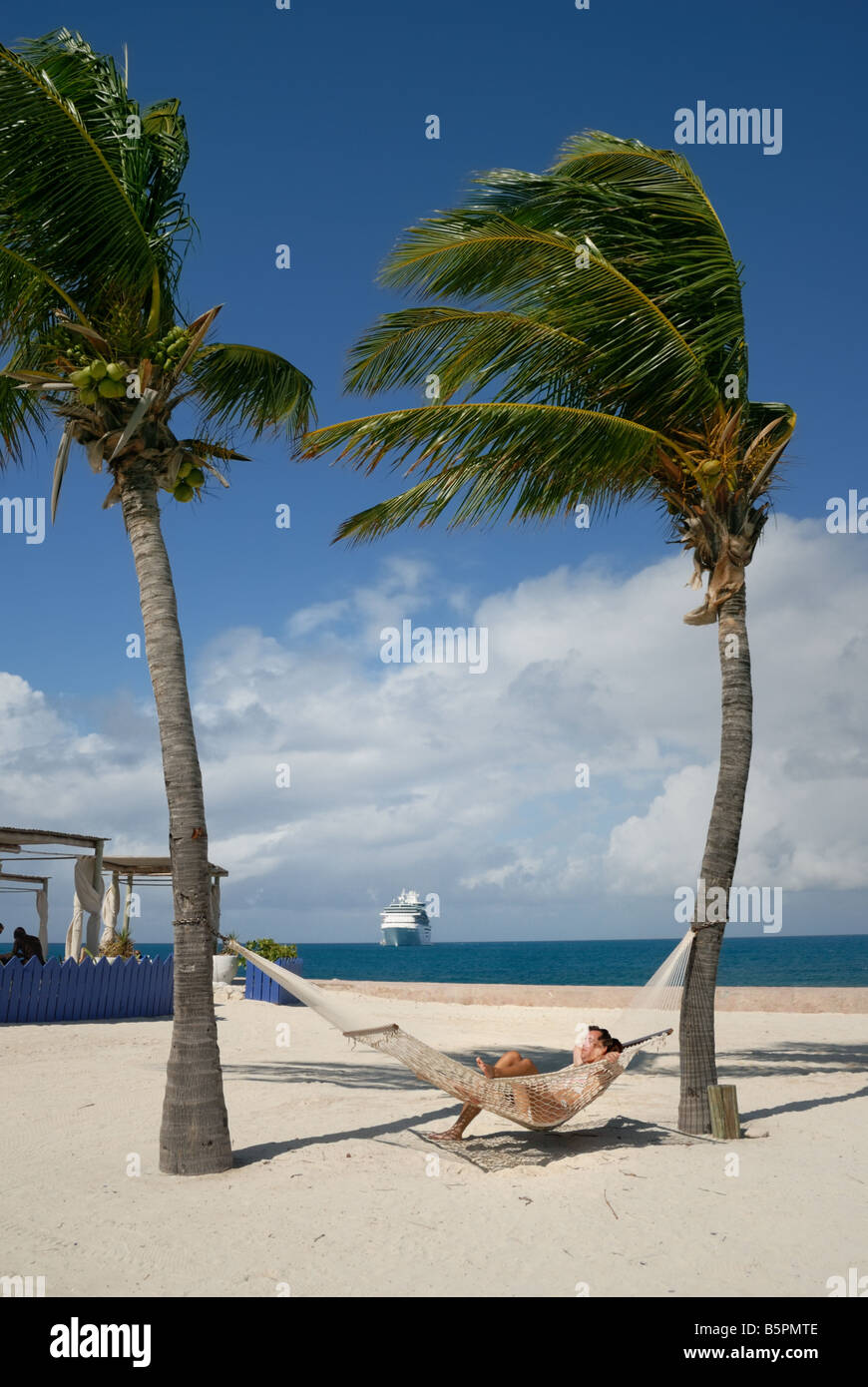A couple lounges in a hammock on the beach at Little Stirrup Cay, Bahamas. - Stock Image