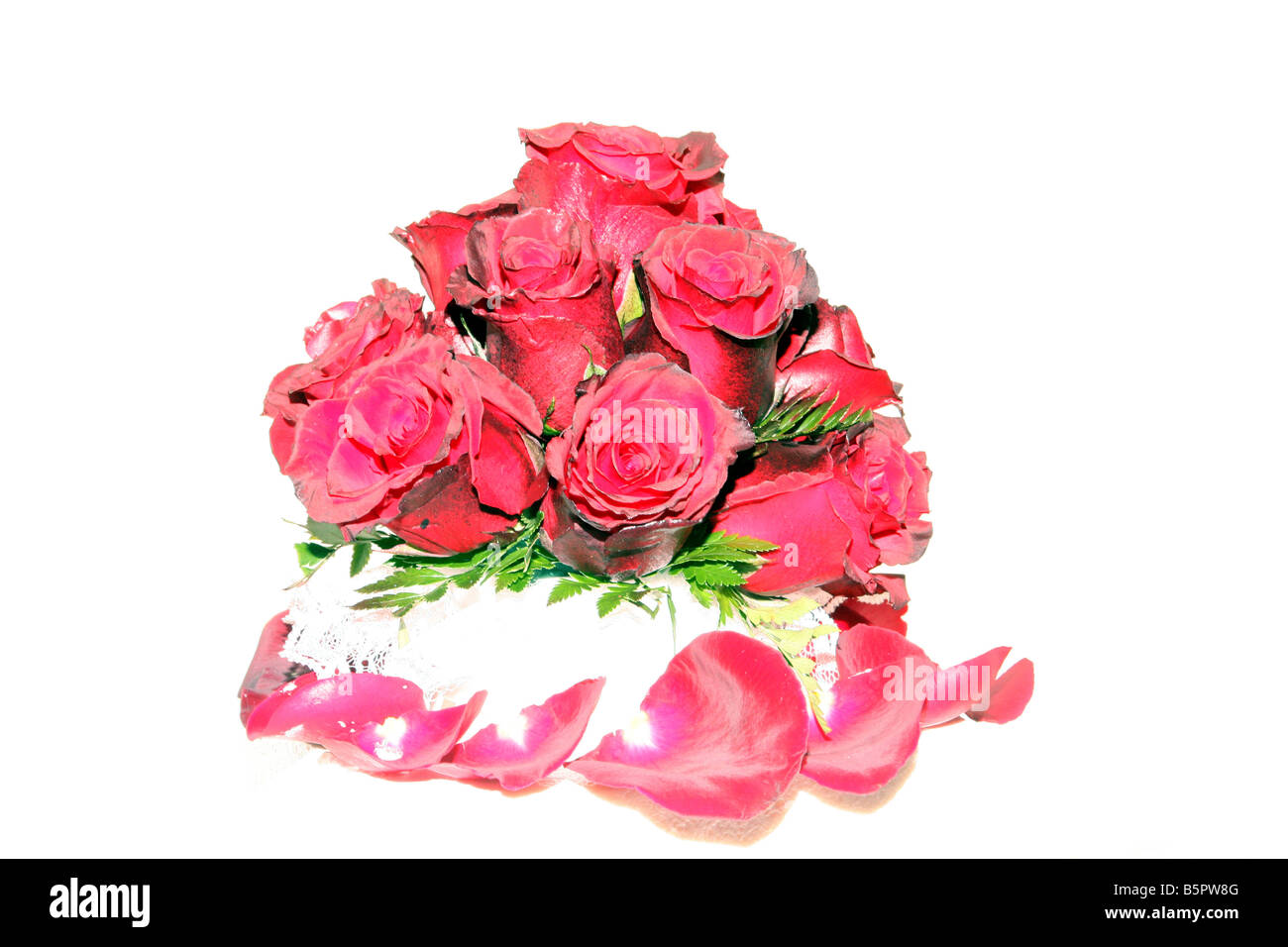 A fancy wedding cake with red roses on top displayed for a wedding reception - Stock Image