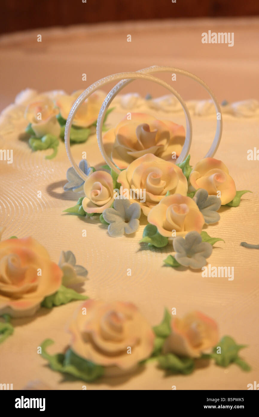 A wedding cake decorated with wedding ring symbols and full of frosting flowers - Stock Image