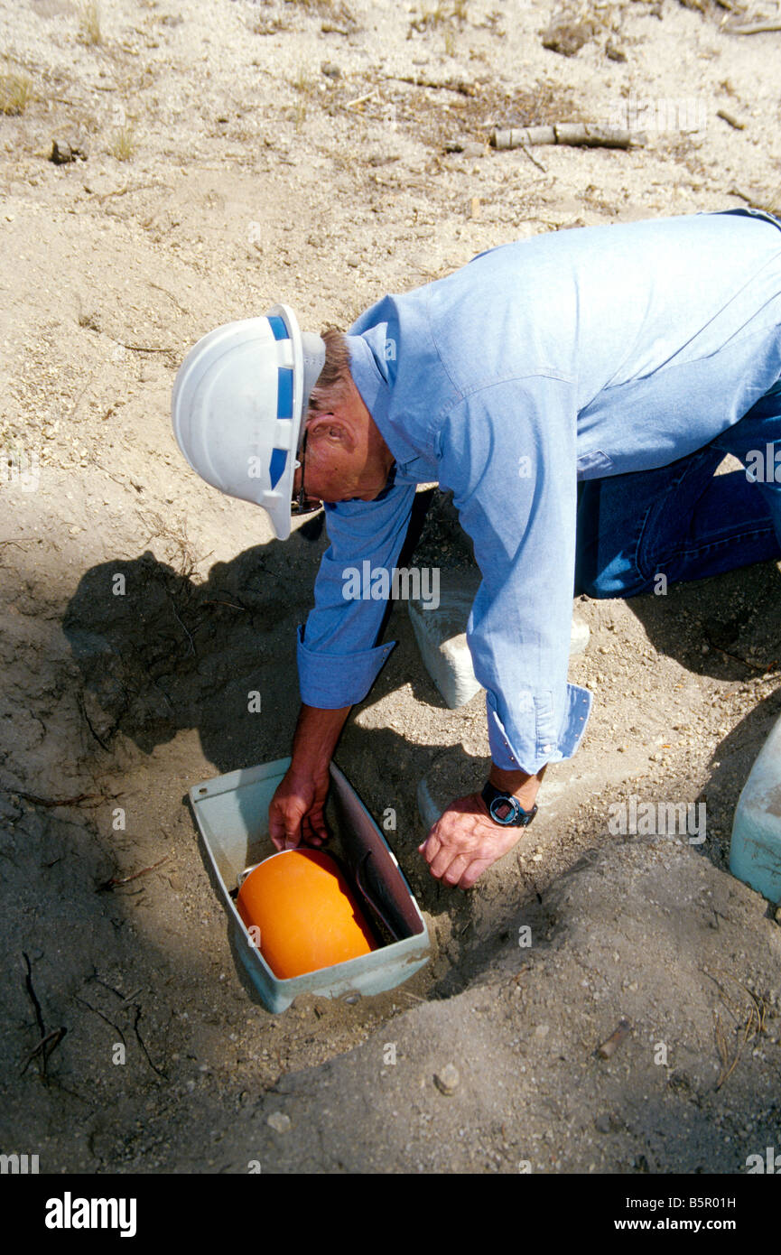 Technician checking seismometer. - Stock Image