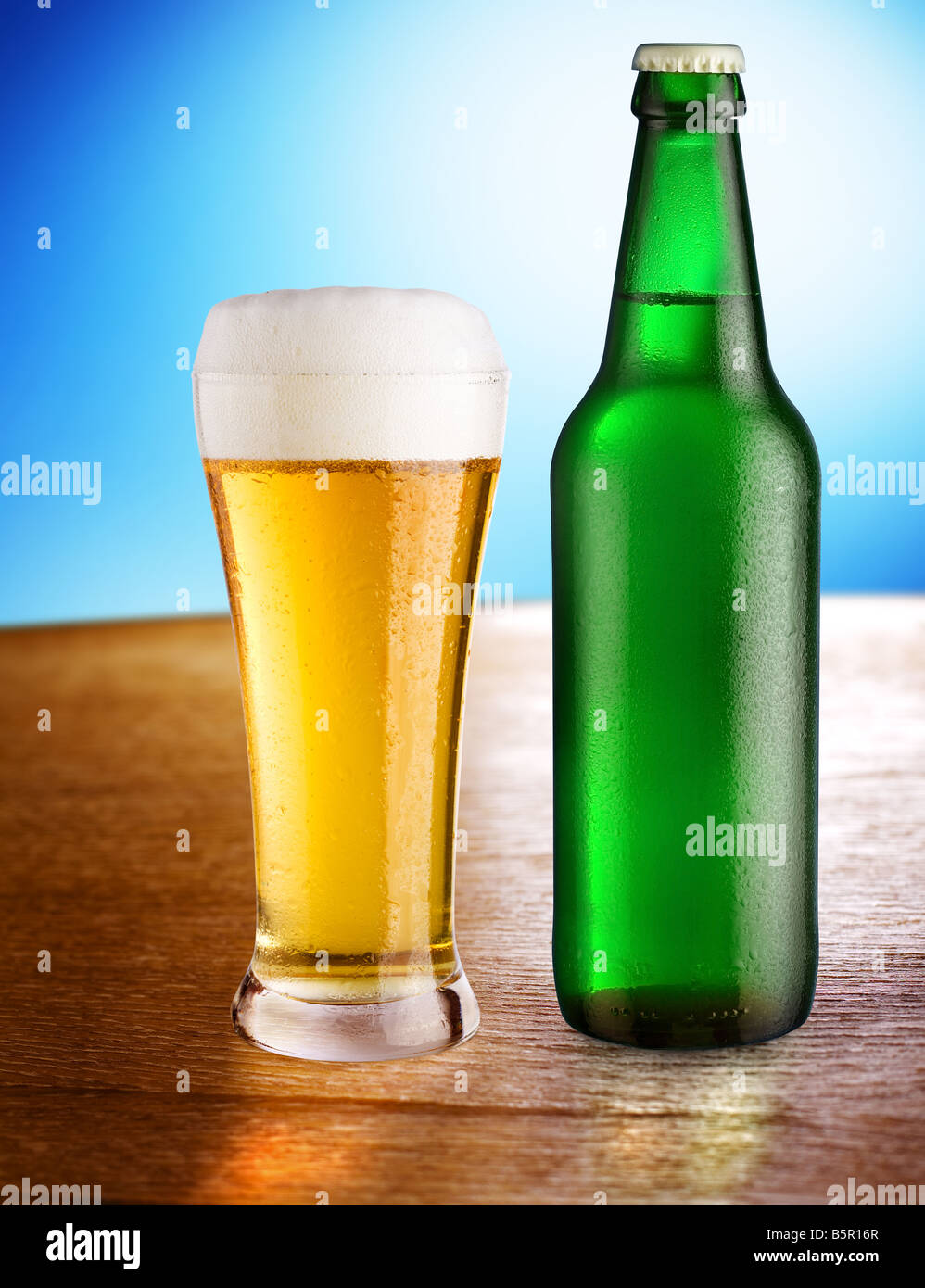 Glass with beer and bottle stand on a table on a blue background Stock Photo