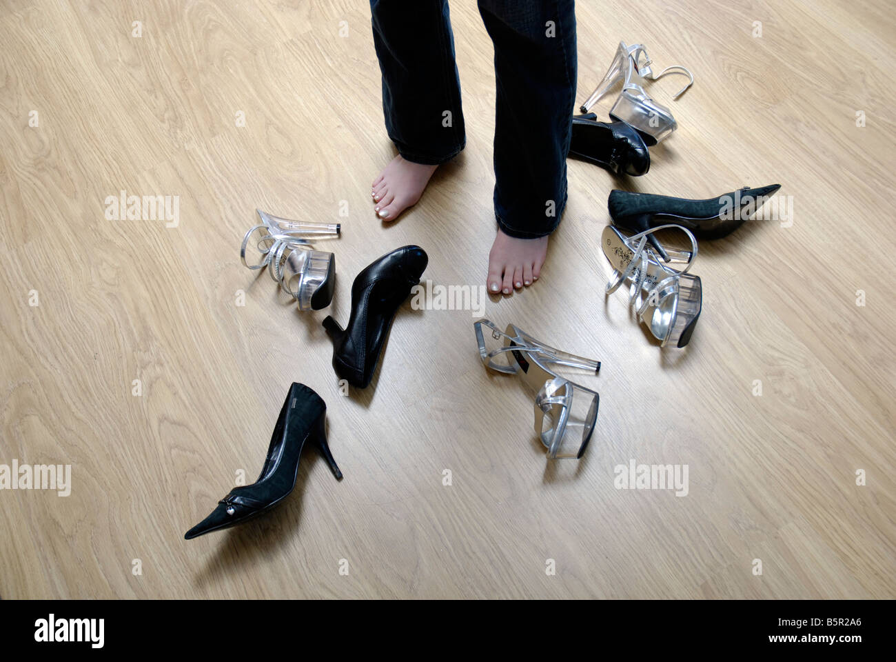 Young woman trying to decide which of her shoes to wear - Stock Image