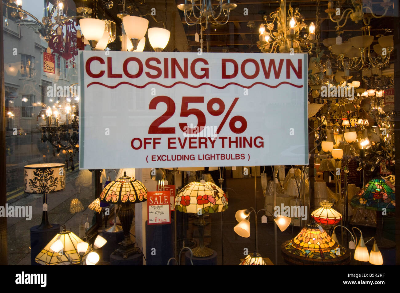 Closing Down sign offering 25 per cent at a lighting shop in Brighton but adding 'Excluding Lightbulbs' - Stock Image
