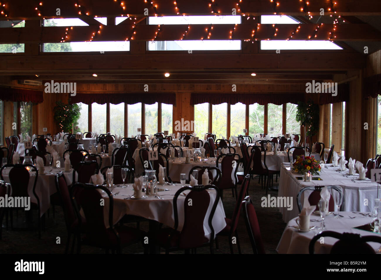 A wedding reception hall set up for a dinner later when the guests arrive to celebrate a wedding ceremony - Stock Image