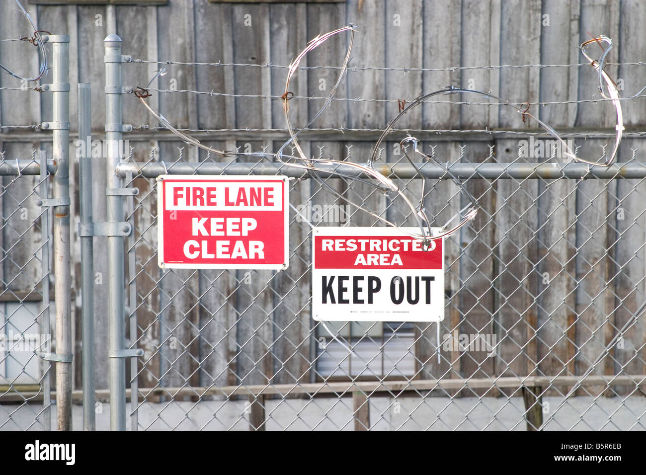 fire lane and restricted area signs on a wire fence - Stock Image