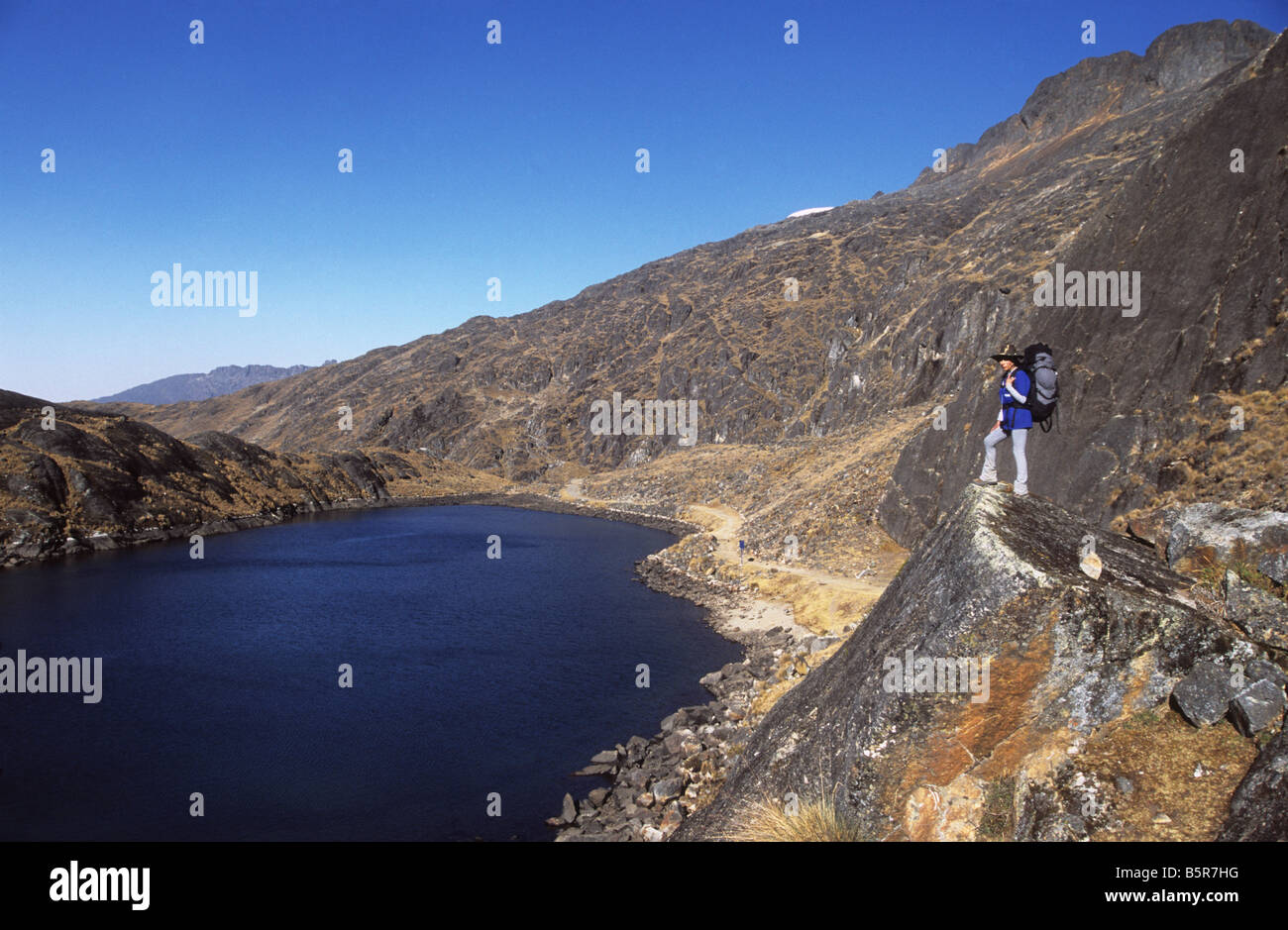 Trekker looking at view over glacial lake on the Takesi Inca Trail, Cordillera Real, Bolivia - Stock Image