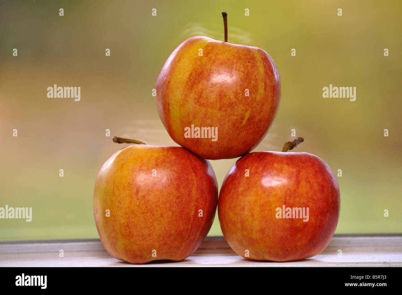 Three apples stacked on a window sill Stock Photo