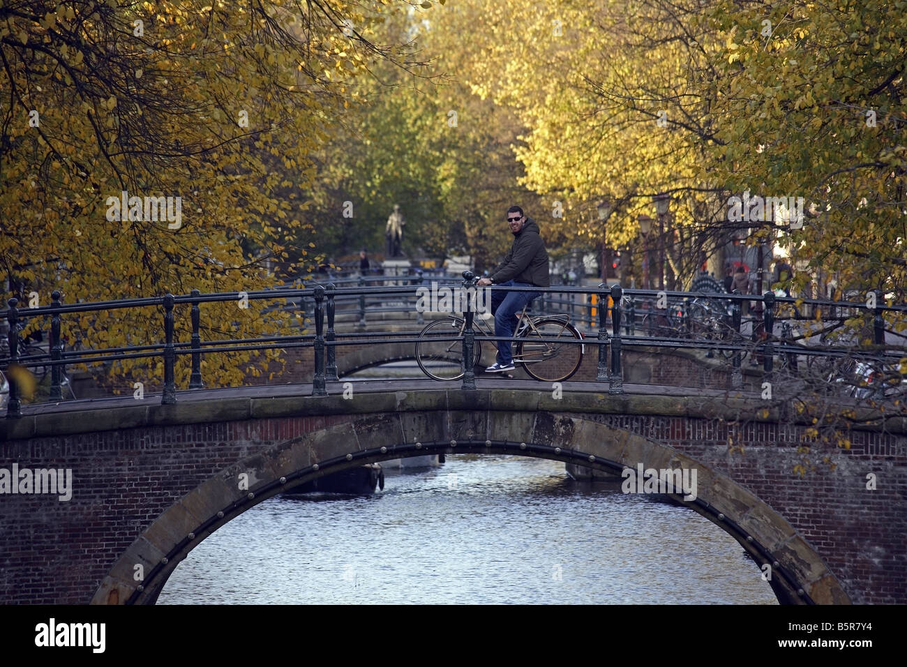 A cyclist driving over the bridge at the Prinsengracht, Amsterdam - Stock Image