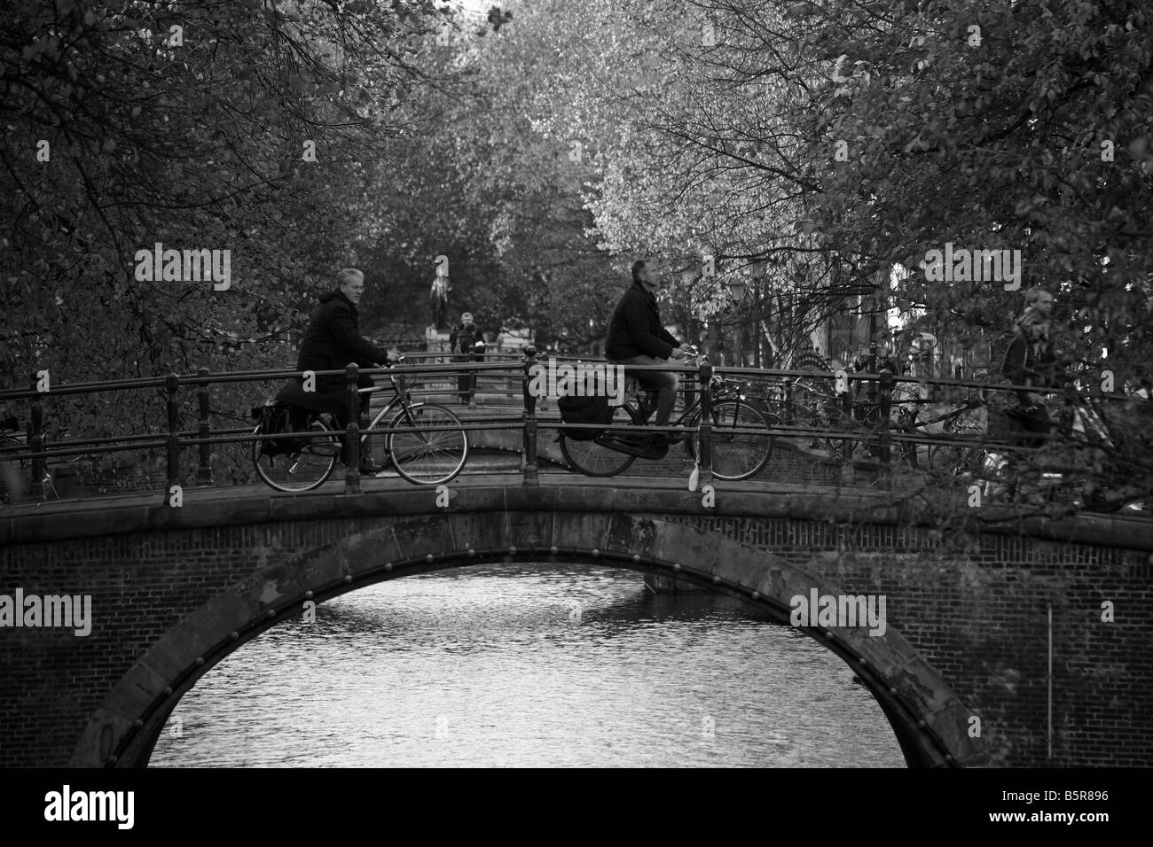 People cycling across the bridge at the Prinsengracht, Amsterdam - Stock Image