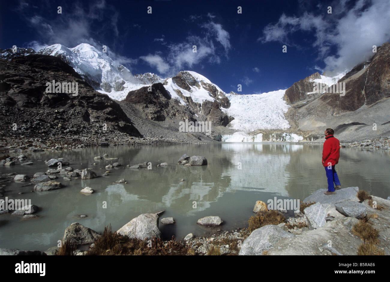 Trekker looking at view at Laguna Glaciar, Mount Illampu in background, Cordillera Real, Bolivia - Stock Image