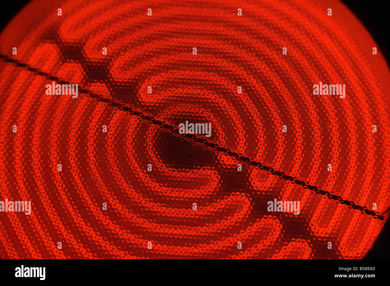 Close up of a red hot glowing electric stove cooking element. - Stock Image