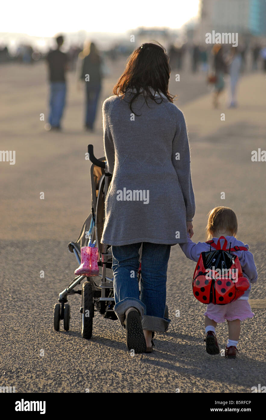 Mother with pushchair and toddler walking alongside. Hove promenade. Model released - Stock Image