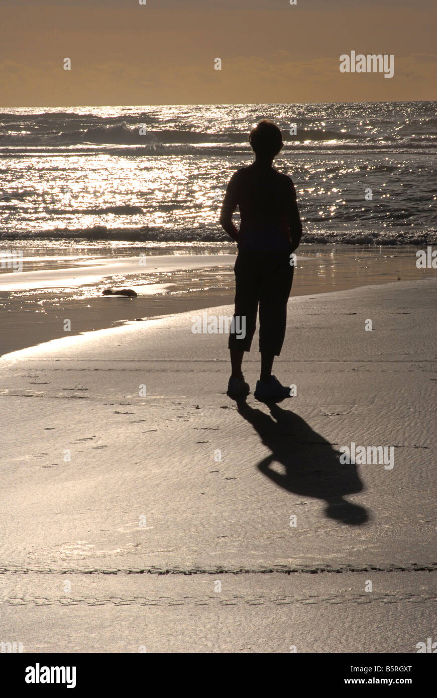 Silhouetted shape of a woman walking along a sandy shore. Grey mouth. New Zealand - Stock Image