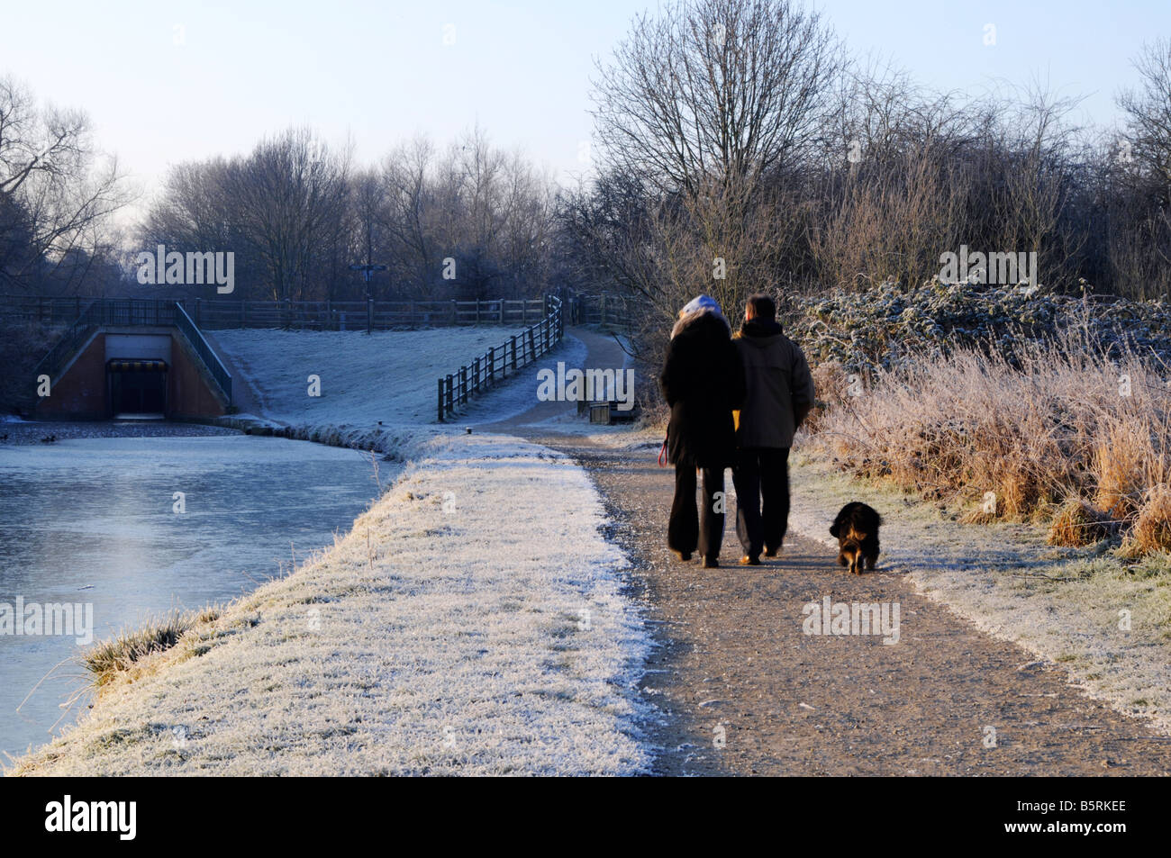 couple walking with dog on the canal towpath on a frosty morning Chesterfield Derbyshire - Stock Image