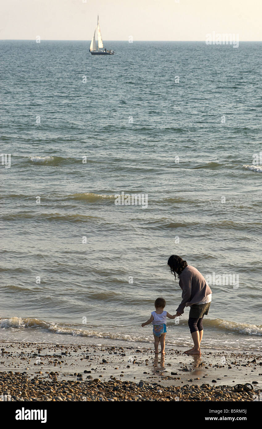 Mother and toddler paddling at low tide. Yacht beyond. Brighton beach, East Sussex, England - Stock Image